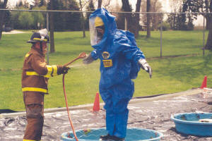 Firefighter hosing off individual wearing hazardous material suit