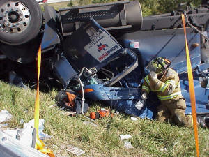 Firefighter helping individual in overturned vehicle